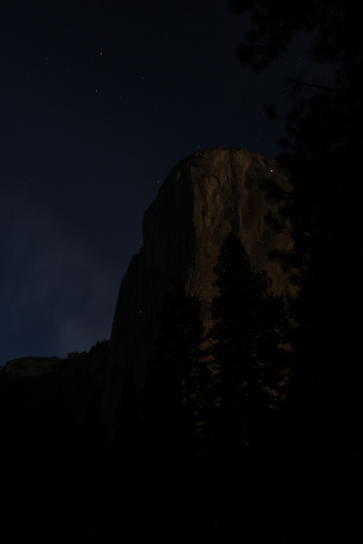 El Capitan lit by moon and decorated by climber torches.